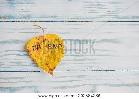 Yellow And Green Leaf With The Inscription The End On The Old Wooden Background