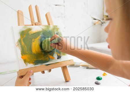 Little creative painter in working process. Early childhood education, artist workplace, interesting hobby for children, art concept