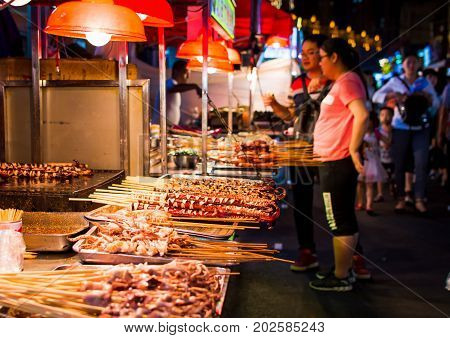 Nanning, China - June 9, 2017: Food On The Zhongshan Snack Street, A Food Market In Nanning With Man