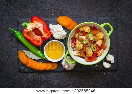 bowl of stewed vegetables ragout and raw ingredients. Healthy Vegetarian Food Concept.