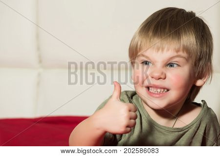Small boy with thumb up. Gesture and emotions. Kid with blonde hair. Childhood and success. Child with angry face.