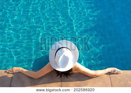 Happy smiling asian woman with straw hat relax and luxury in swimming pool at resort hotel lifestyle and happy day. Summer Concept