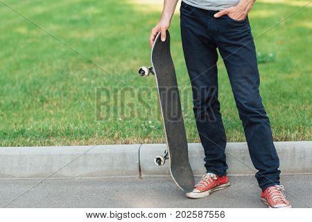 Unrecognizable hipster man with skate. Summer extreme sport challenge and competition for fun, modern urban lifestyle and culture