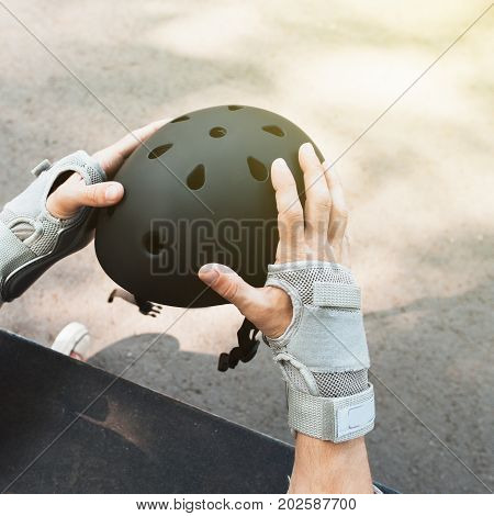 Skateboard halmet and gloves protection on unrecognizable skateboarder. Extreme sport challenge and self-confidence, motivation for win in competition