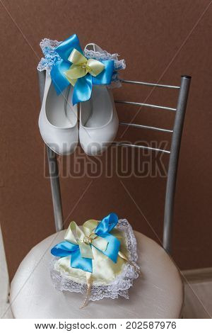Bridal accessories on a white chair with flowers, perfume shoes. Clothing concept