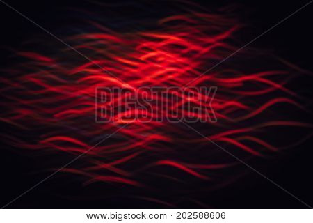 Abstract background of red waves in motion on black. Bokeh of defocused curves, blurred neon leds similar to sea fauna, serpantine of fish, migration backdrop