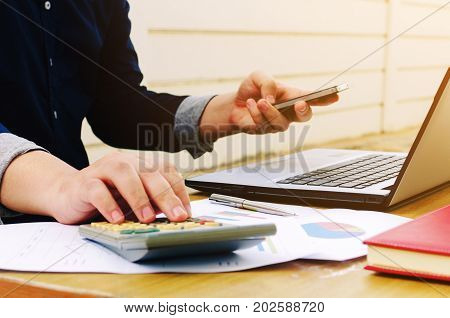 young business man or accountant working with laptop computer mobile smart phone calculator and business document report on desk savings money business finances and economy concept