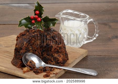 christmas pudding on a cutting board with cream