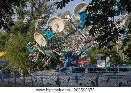 Donetsk Ukraine - August 27 2017: Townspeople riding amusement rides in the Shcherbakov park during the celebration of the City Day