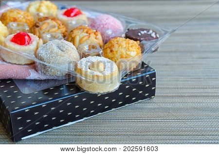 Different Panellets on wooden background. Typical sweets consumed at All Saints Day (Dia Todos Los Santos) in Catalonia Spain. Catalan small cakes or cookies made mainly of marzipan rolled in pine nuts.