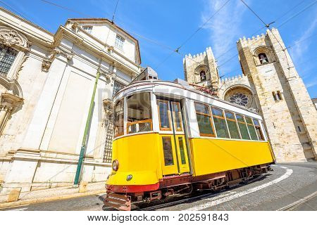 Historic tram line in front of Lisbon Cathedral in Alfama district, Lisbon, Portugal. Lisbon street with typical yellow vintage tram and Se de Lisboa. Icons and symbols of the Portuguese capital.