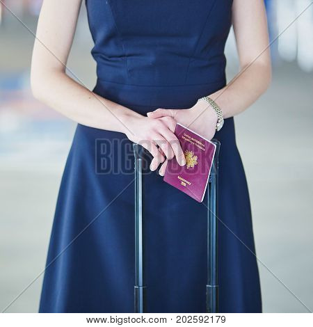 Woman In The International Airport Holding French Passport In Her Hands