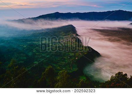 Landscape of Cemoro Lawang village and fog during sunrise in Bromo Tengger Semeru National Park East Java Indonesia