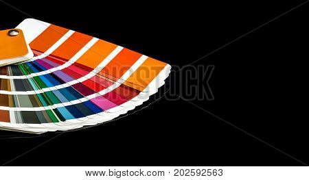 Color swatches book on a black reflective background.
