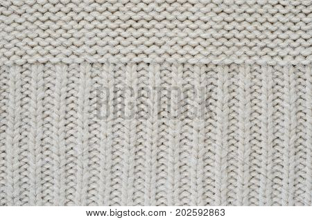 Texture of a beige knitted sweater close-up. Vertically oriented pigtails on knitted fabric