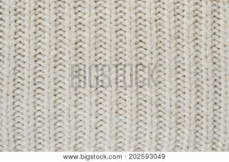Texture of a beige knitted sweater close-up. Vertically oriented pigtails on knitted fabric. Uniform knitting pattern