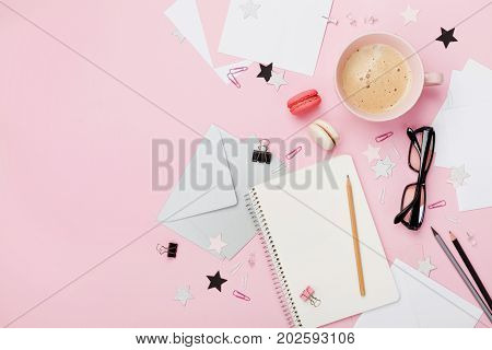 Coffee macaron office supply and clean notebook on pink pastel table top view for blogging. Flat lay style. Beautiful morning breakfast. Fashion woman working desk.