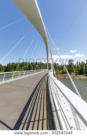 Details of white suspension bridge over water in summer
