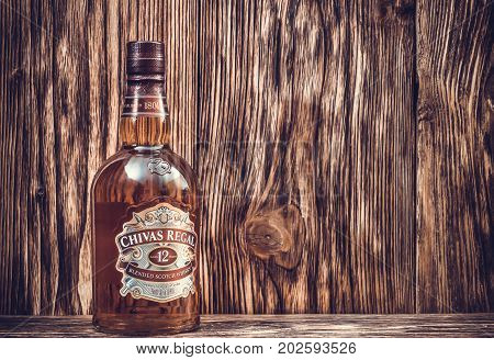 Ternopil Ukraine - August 26 2017: Bottle of Blended scotch whisky Chivas Regal. 12 years old scotch whiskey. Made in Scotland. Bottle of whisky on wooden background. Toned.