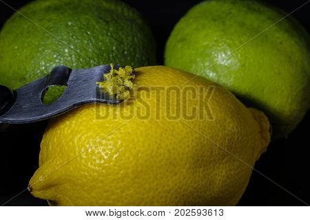 Close-up of a stainless steel zester with one lemon and two limes on black background