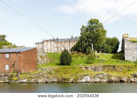 Old pinkish mansion behind water on top of a hill in Suomenlinna Finland