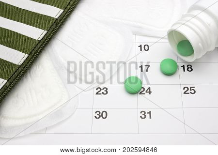 Menstruation pads menstrual calendar and green pills. Green pharmaceutical tablets spilling out of a white pill bottle. Menstrual period pain protection. Contraceptive birth control hormone pills
