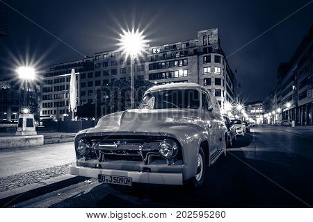 BERLIN GERMANY - OCTOBER 13 2015: Full-size pickup truck Ford F100 Panel Van 1953 (second generation) on the night street. Stylization. Toning. Ford F-Series - is a popular American pickup.