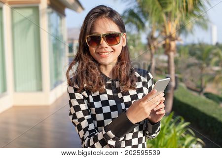 young asian woman wearing sun glasses and smart phone in hand toothy smiling face