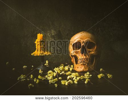 Still life with human skull and candle on abstract background