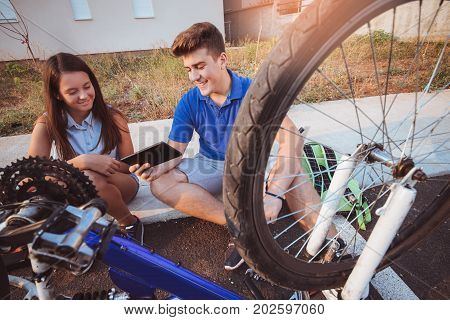 Teenager boy repair tire on bicycle female friend sitting next to him using digital tablet for instructions summer outdoor photo