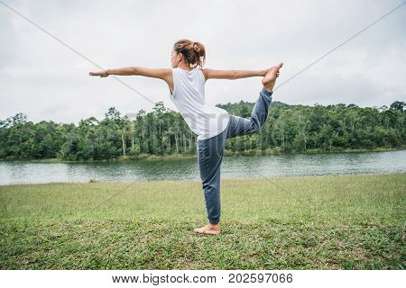 Asian women relax in the holiday. Play if yoga. on a green pasture.