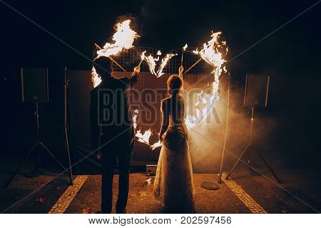 the bride and groom light a fire heart