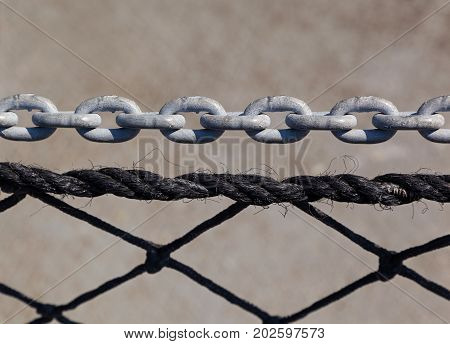 Black rope and corroded silver chain with a beige background with space for text.