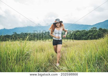 Asian women travel relax in the holiday. on a green pasture.