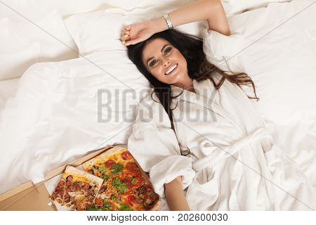 Pretty young sexy fashion sensual woman posing on white background.Sensual woman in white bathrobe. White bed isolated, crazy night party time,girl eating tasty pizza