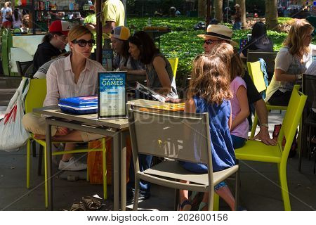 New York NY USA August 3 2016 --People sitting around the game tables in Bryant Park on a summer day in Manhattan. Editorial Use Only.