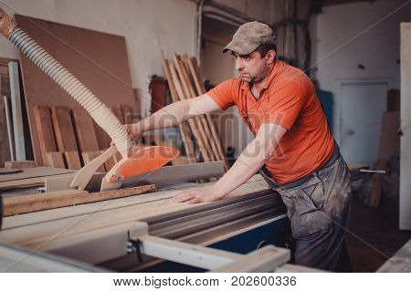 A carpenter works on woodworking the machine tool. Man collects furniture boxes. Saws furniture details with a circular saw. Process of sawing parts in parts. in side view