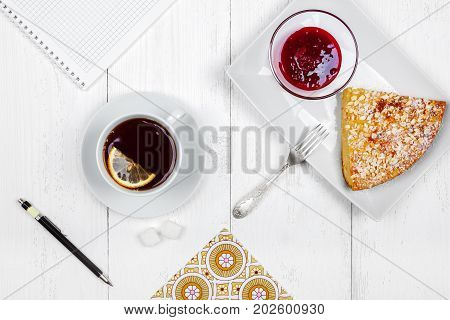 Cheesecake raspberry jam and black tea with lemon close-up. Light breakfast or snack top view