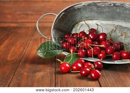 Sweet cherries with leaves scattered on table