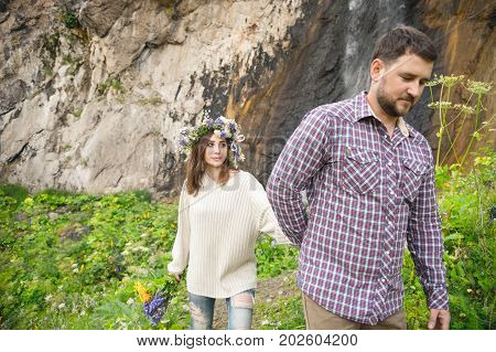 Hipster with a beard leads his bride in the nature against the background of a waterfall falling from a rock