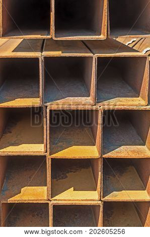 The manufactured by welding square rusty steel pipes piled up warehouse outdoor