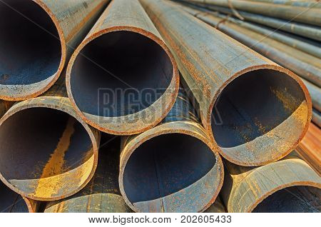 The manufactured by welding round rusty steel pipes piled up warehouse outdoor