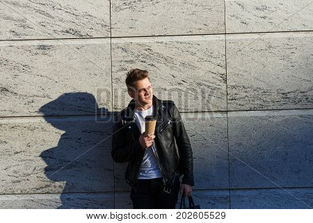 Lifestyle outdoor shot of handsome joyful young Caucasian man carrying bag in one hand and holding papercup of coffee or tea in other waiting for friend standing against blank wall background