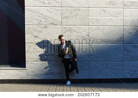 Full length portrait of stylish European male student dressed in trendy outfit standing outside of university building holding bag and papercup of takeaway coffee having rest outdoors during break