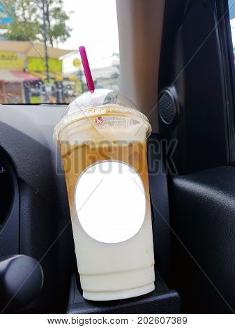 The beverage on Cup holders in carstransportation and vehicle concept - take away cup of iced coffee put on a front console of a car with water drop of rainingboost the energy to drive