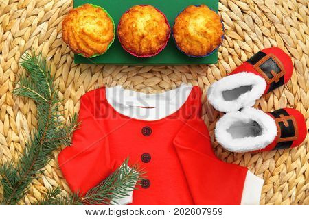 Baby Santa costume and tasty muffins on wicker mat