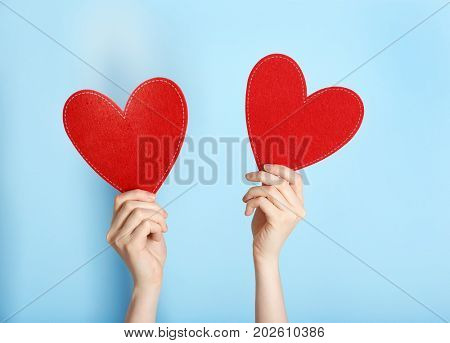 Woman holding red hearts on color background. Volunteer concept