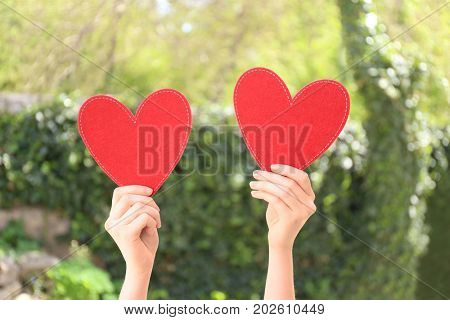Woman holding red hearts on blurred background. Volunteer concept