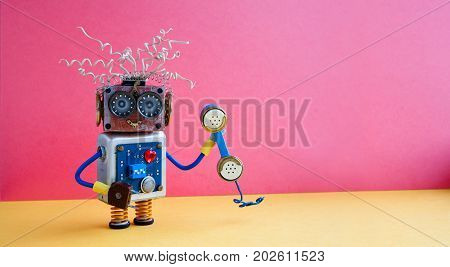 Customer service call center operator concept. Friendly robot assistant with retro styled phone on yellow pink background. copy space photo.