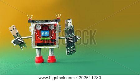 Backup storage information concept. Robot with portable devices usb flash stick. Macro, green yellow gradient background.